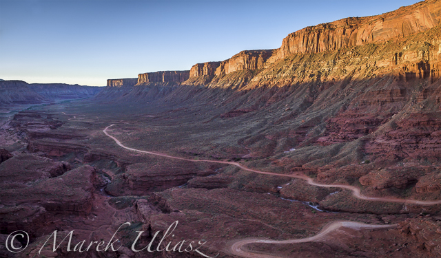 aerial view of a windy road through red sandstone canyon with coarse vegetation near Moab, Utah